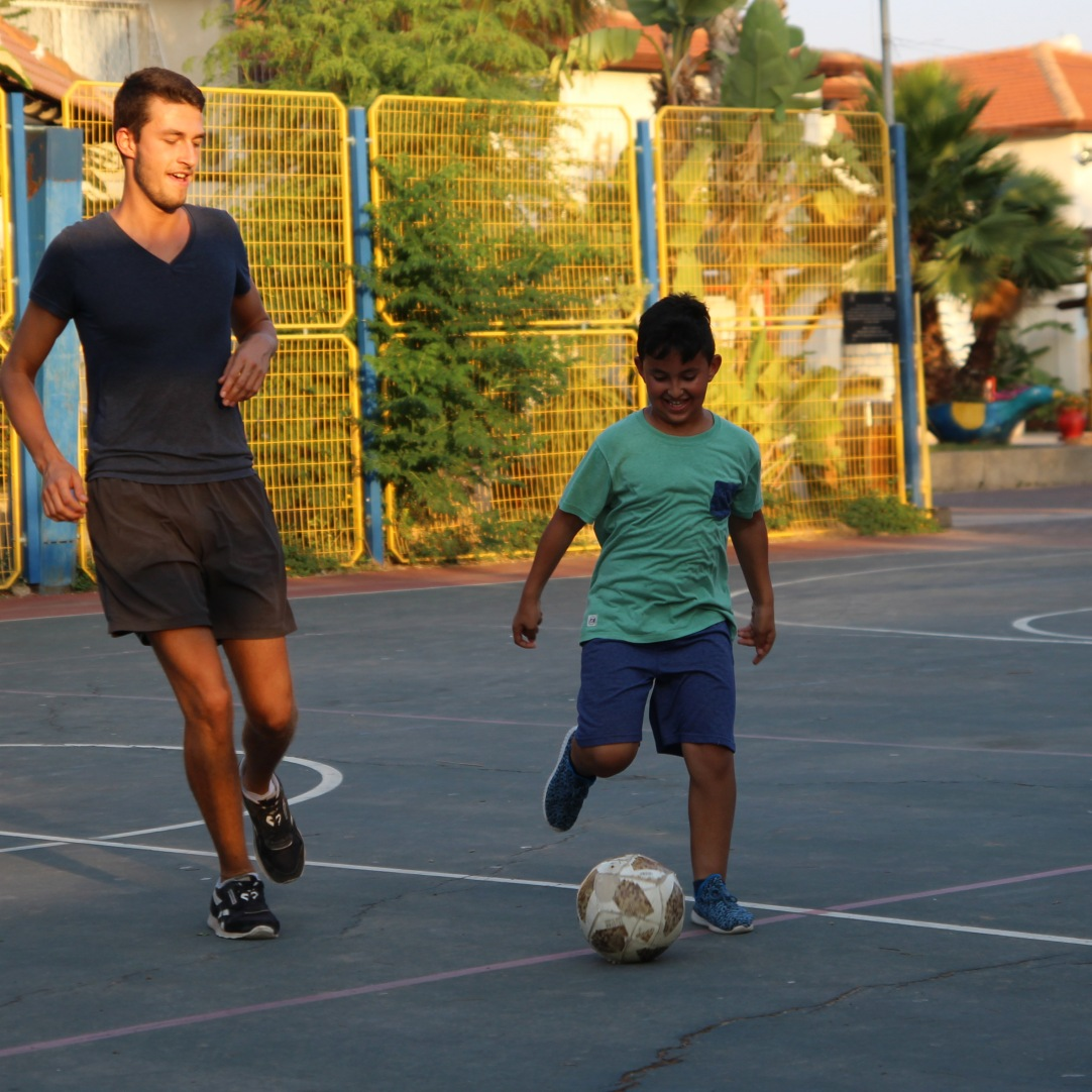 German volunteer Louis playing soccer with the children.